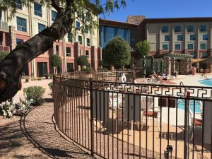 A decorative wrought iron pool fence secures a hotel's pool area.
