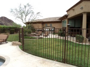 Brown wrought iron fence secures a residential swimming pool.