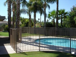 Wrought iron fencing encloses a residential pool.