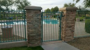 Turquoise-colored wrought iron pool fence and gate secure a community pool area.