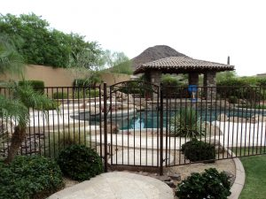 Wrought iron pool fence and gate secure a residential pool area.