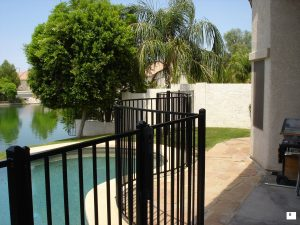 A black wrought iron pool fence secures a backyard swimming pool.